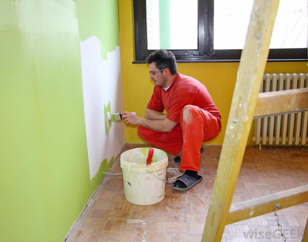 man-in-red-jumpsuit-painting-a-wall-green